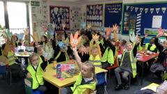 Class 2 children holding up dinosaur footprints