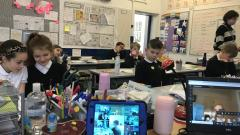 children learning in class and on screen at home